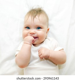 Smiling baby sucking his finger on a white bed.