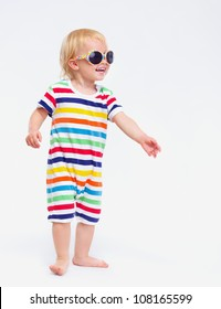 Smiling baby in swimsuit and sunglasses looking on copy space