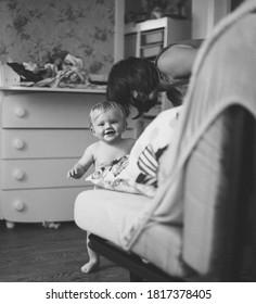 bébé souriant marchant près d'un canapé à la maison