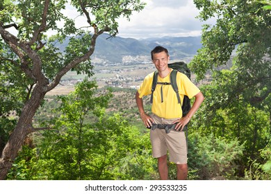 Smiling backpacker in the forest looking at camera