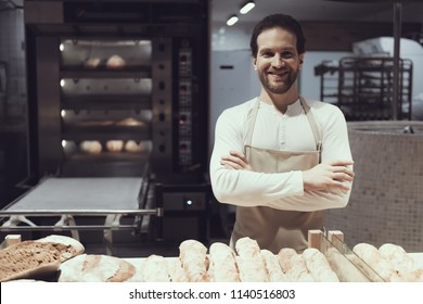 Smiling Baker in Bakery Department in Supermarket. Bearded Man in Apron. Fresh Bread. Worker in Hypermarket. Worker of Supermarket Concept. Loaf of Bread. Fresh Food Concept. Working Man.