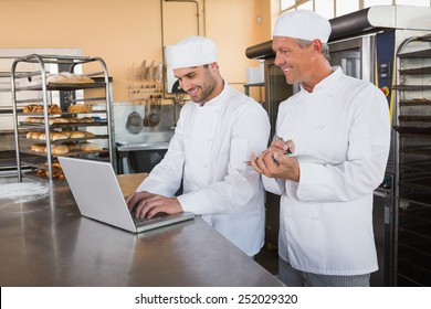 Smiling bakers working together on laptop in the kitchen of the bakery