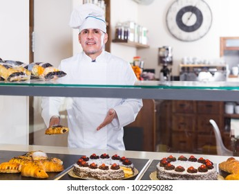 smiling bakery male worker with delicious pies and rolls on counter in the shop