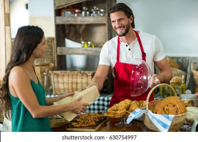 Smiling bakery staff giving parcel to a female customer at counter in bake shop