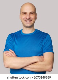 smiling bald man wearing blue t-shirt looking at camera. Happy guy with arms crossed. Isolated on grey
