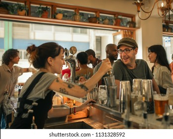 Smiling bar patron ordering drinks from a female bartender mixing cocktails behind the counter of a trendy bar