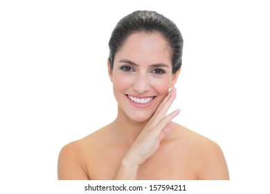 Smiling bare brunette touching her right cheek on white background