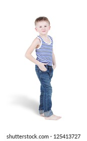 Smiling barefooted boy in striped singlet and jeans stands with his hands in pockets