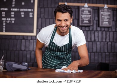 Smiling barista cleaning counter in the bar