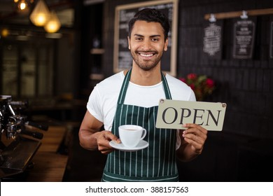 Smiling barista holding coffee and open sign in the bar