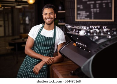 Smiling barista leaning against counter in a cafe