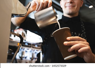 smiling barista man pouring whipped milk from frothing pitcher in paper cup with coffee standing in front of professional coffee machine in cafe