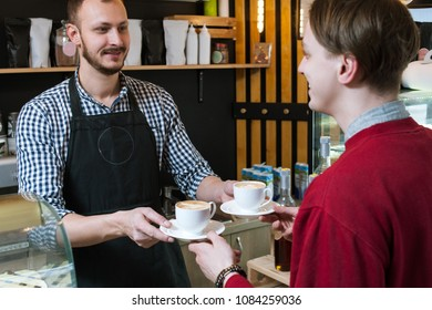 smiling barista serving a cup of freshly made coffee to a client. hipster young man visiting coffee shop