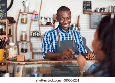 Smiling barista standing behind a counter in a cafe taking a credit card from a customer to pay for her purchase