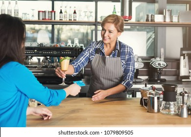 Smiling barista taking credit card from customer to pay for beverage at coffee shop counter. Small business, occupation people, payment and service concept, copy space