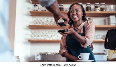 Smiling barista using nfs technology to help a customer pay for a purchase with their bank card in a cafe