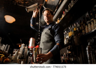 Smiling barman pouring alcoholic drink from one metal glass into another on the background of bar counter. Bottom view