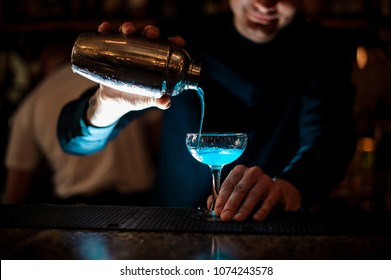 Smiling barman pouring fresh drink with blue liquor from a shaker into a glass using a strainer on the bar counter