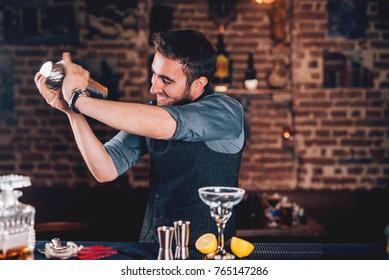 Smiling barman using shaker for cocktail preparation. Portrait of barman making tequila based margarita at local pub