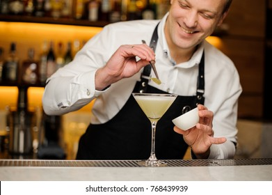 Smiling barman in white shirt and apron decorating a cocktail glass with a tiny birch leaf