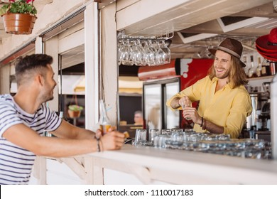 smiling bartender and client with beer bottle looking at each other in beach bar