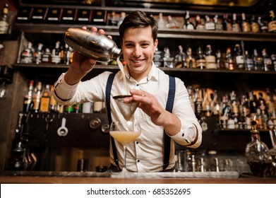 smiling bartender with fancy cocktail and shaker