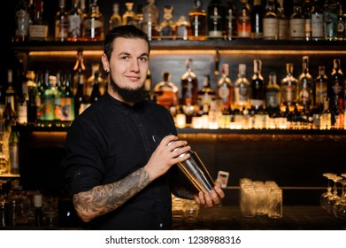 Smiling bartender holding a steel shaker standing on the background of the bar shelf with a lot of alcohol bottles