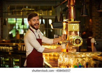 Smiling bartender pours a beer indoors