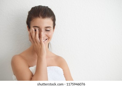 Smiling bashful young woman wrapped in a clean white towel holding her hand to her face with closed eyes against a white interior wall with copy space