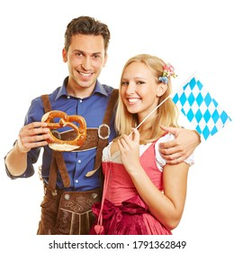 Smiling Bavarian couple in traditional costume with pretzels and flag for Oktoberfest