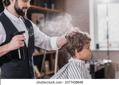smiling bearded barber combing and spraying hair of little kid
