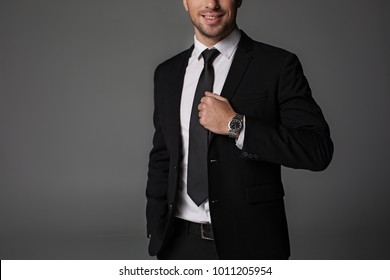 Smiling bearded businessman demonstrating modern watch on hand. Time concept. Isolated