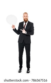 smiling bearded businessman holding blank speech bubble and pointing with finger isolated on white