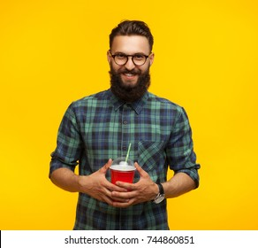 Smiling bearded hipster man looking at camera and holding plastic cup.