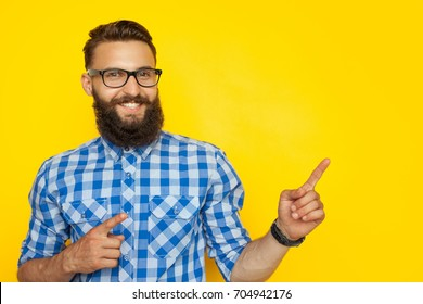 Smiling bearded hipster man pointing on side on colorful yellow background.