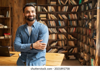Smiling bearded indian businessman stands near desk and looks at the camera. Young positive male student in library with bookshelves on background. Proud and successful mixed-race small business owner