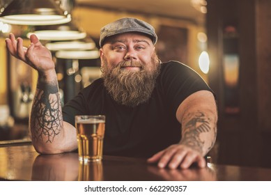 Smiling bearded male drinking beer in pub