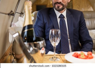Smiling bearded male sitting in airplane seat at tray table with champagne and strawberry. Focus on man