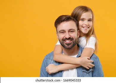 Smiling bearded man in casual clothes have fun with cute child baby girl. Father little kid daughter isolated on yellow background in studio. Love family day parenthood childhood concept. Hugging