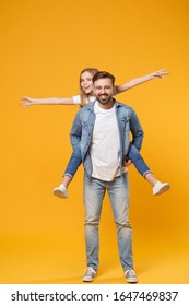 Smiling bearded man with child baby girl. Father little kid daughter isolated on yellow background. Love family parenthood childhood concept. Give piggyback ride to joyful sit on back spreading hands