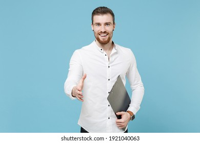 Smiling bearded man guy 20s in white shirt isolated on blue background. People lifestyle concept. Mock up copy space. Hold clipboard with papers document, standing with outstretched hand for greeting