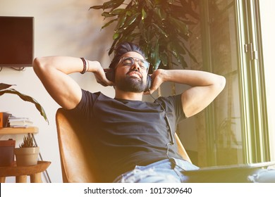 Smiling bearded man in headphones listening to music on tablet at home. Relaxing and rest time concept. Blurred background