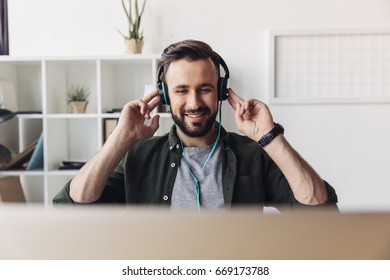 Smiling bearded man listening music in headphones while sitting in office