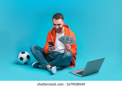 Smiling bearded man making bets online using application on his mobile phone. Lucky winner holding ward of dollar banknotes in hand.