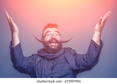 Smiling bearded man with a mohawk hairstyle and a very long mustache raising hands up in the sunlight