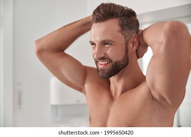Smiling bearded man with muscular chest strokes hair posing for camera in bathroom