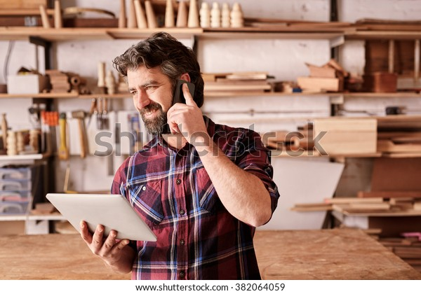 Lächelender bärtiger Mann, Besitzer eines kleinen Holzwerkgeschäftes, in seinem Werkstattstudio stehend, auf seinem Handy telefonieren und eine digitale Tablette halten