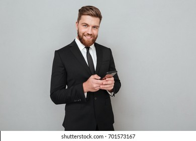 Smiling bearded man in suit using his smartphone and looking at the camera over gray background