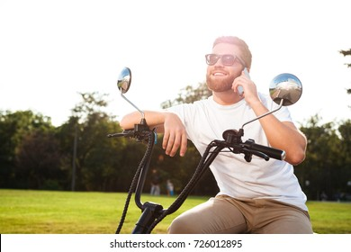 Smiling bearded man in sunglasses sitting on modern motorbike outdoors and talking by the smartphone
