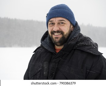 Smiling bearded man traveler on snow-covered field background